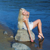 Girl on the rock. Romantic beautiful sweet girl sitting on a rock by the sea and enjoy Stock Photos