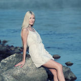 Girl on the rock. Romantic beautiful sweet girl sitting on a rock by the sea and enjoy Royalty Free Stock Images