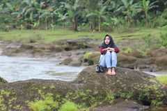 Girl on rock. She& x27;s sitting on the rock of the kampili dam and river, gowa regency, south sulawesi Royalty Free Stock Image