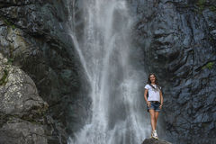 Girl on rock with waterfall background Royalty Free Stock Images