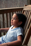 Girl in Rocking Chair. A girl rocks on the porch Stock Photo