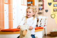 Girl rocking rocker horse Royalty Free Stock Photography
