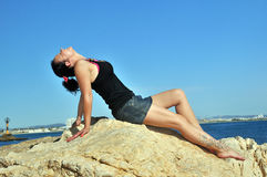Girl on the rocks by the sea Royalty Free Stock Photo