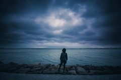 Girl on rocks beside the sea Royalty Free Stock Images