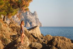 The girl on the rocks at sea stock images