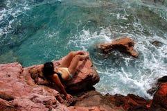A girl on rocky beach Stock Image