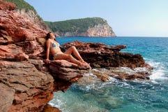 A girl on rocky beach Stock Photography