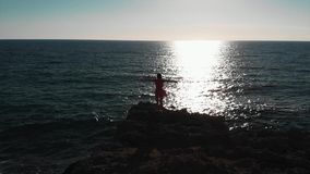 Girl on rocky beach. Young woman standing on ocean cliffs. Girl in red dress at sea. Attractive woman looking at sunset. Beautiful stock footage