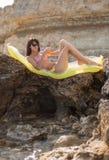 Girl on rocky seashore Stock Photo