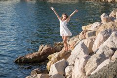 Girl on rocky seashore in sunny day. Vigorous female person in white sleeveless dress posing with arms raised on stony beach in morning time stock photography