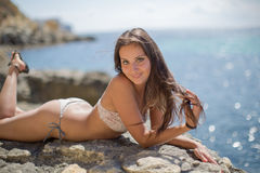 Girl on rocky seashore. Young woman in bikini posing on the beach looking at camera smiling Royalty Free Stock Photos