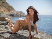 Girl on rocky seashore. Young woman in bikini posing on the beach looking at camera smiling royalty free stock images