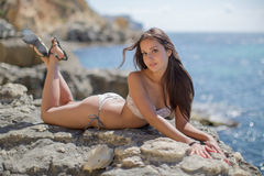 Girl on rocky seashore. Young woman in bikini posing on the beach looking at camera smiling Royalty Free Stock Photo
