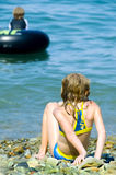 Girl on rocky shoreline. Back of a young girl watching boy in a rubber raft from a rocky shoreline Stock Images