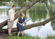 The girl with a rod and the guy looks at it Stock Photography