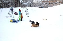 The girl rode a sled to the end of the slide. Winter fun. The action takes place on the outskirts of the city of Monino. Residents of the town come with stock image