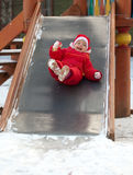 Girl roll down on playground slide Royalty Free Stock Images
