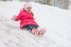 The girl rolled down the ice slide. Seven-year girl riding on a snowy icy hill Stock Photos