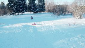 The girl rolled off the slide on the tubing. Happy family rides and smiling snowtube on snowy roads.slow motion. snow winter landscape. outdoors sports stock video