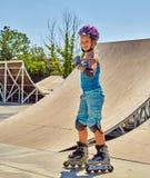 Girl roller skate helmet walking park. Child riding on roller skates. Stock Photos