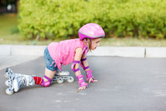 Girl in roller skates getting up Royalty Free Stock Photography