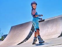 Girl roller in skates park. Child wear safety helmet do sport exercise. Stock Photos