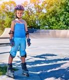 Girl roller in skates park. Child wear safety helmet do sport exercise. Royalty Free Stock Photos