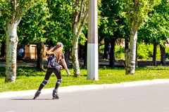 A girl on roller skates is riding on the road stock images