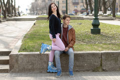 Girl in roller skates sitting on the lap of a guy. Stock Image