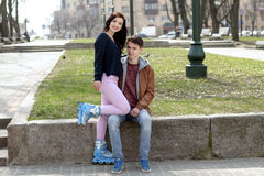 Girl in roller skates sitting on the lap of a guy. Stock Photography