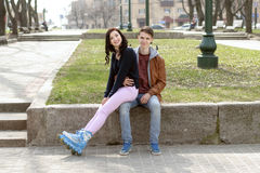 Girl in roller skates sitting on the lap of a guy. Stock Photos