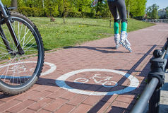 Girl roller-skating and bicycler on the bike path Royalty Free Stock Photo