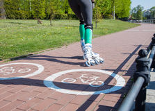 Girl roller-skating on the bike path Royalty Free Stock Photography