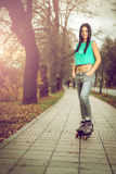 Girl roller skating in park. Young adult teenage girl doing roller skating in park during winter Stock Image