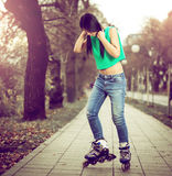 Girl roller skating in park. Young adult teenage girl doing roller skating in park during winter Royalty Free Stock Photo