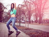 Girl roller skating in park. Young adult teenage girl doing roller skating in park during winter Stock Images