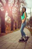 Girl roller skating in park Stock Photos