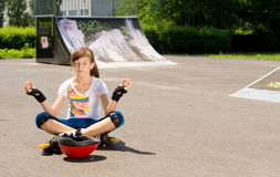 Girl in rollerblades sitting meditating Royalty Free Stock Photography