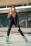 Girl on rollerblades standing in building background. Royalty Free Stock Photo