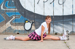 Girl in rollerskates stretching outdoor Stock Images