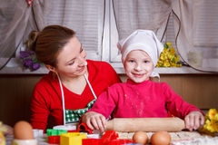 Girl rolling dough with her mother. Cute girl rolling dough with her mother stock image