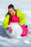 Girl rolling a huge snowbal Royalty Free Stock Image