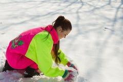 Girl rolling a huge snowbal Stock Photos