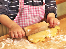 Girl rolling out the dough. Photo shows a close up of a girl rolling out the dough and preparing the christmas butter cookies Royalty Free Stock Image