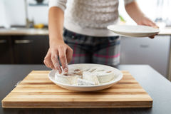 Girl rolls fish in flour to fry Stock Photography