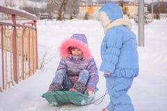 The girl rolls her older sister sledding Stock Image