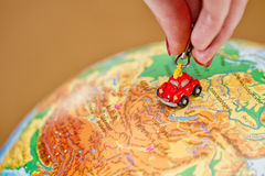 Girl rolls a little toy car on the globe Royalty Free Stock Photo