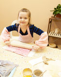 Girl rolls out the dough Royalty Free Stock Photo