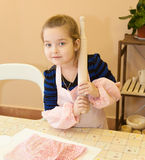 Girl rolls out the dough Stock Images