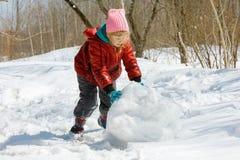 Girl rolls a snowball Stock Photography